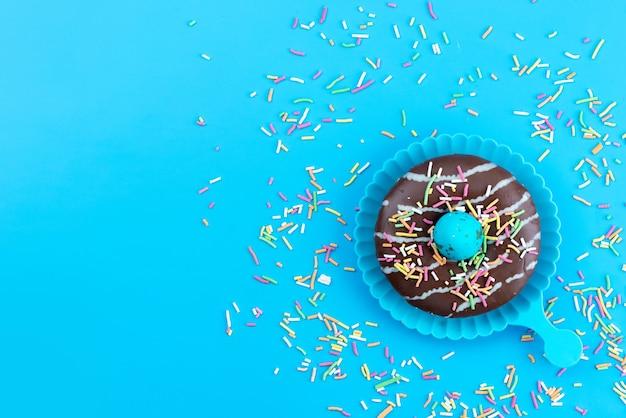 Uma vista de cima rosquinhas doces deliciosas e chocolate à base de doces na mesa azul, bolo de chocolate cor de biscoito