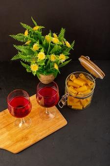 Uma vista de cima, taças de vinho na mesa de madeira marrom, junto com flores e massa italiana crua na mesa escura, bebem bebida alcoólica