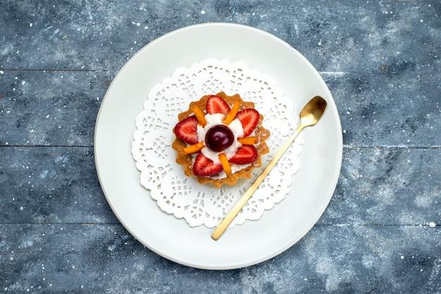 Uma vista de cima, um pequeno bolo delicioso com creme e frutas em um prato branco sobre o biscoito de bolo de frutas cinza-azulado