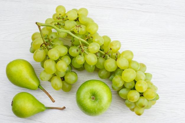 Uma vista de cima uvas verdes frescas com peras e maçã na mesa branca frutas cor verde verão