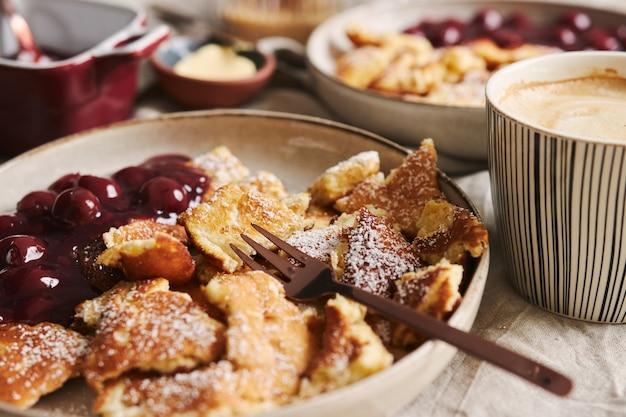 Uma vista de deliciosas panquecas fofas com cereja e açúcar de confeiteiro