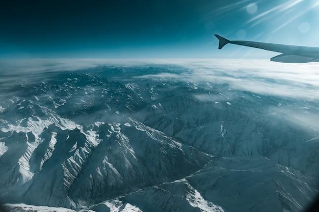 Uma vista de montanha de inverno da janela do avião