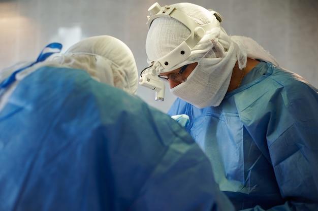 Uma vista de perfil do cirurgião-chefe com uma lâmpada na cabeça