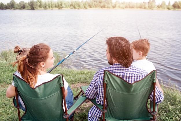 Uma vista de trás. pais felizes estão segurando seus filhos de joelhos. os adultos estão sentados em cadeiras dobráveis e se entreolham. as crianças estão segurando varas de peixe nas mãos.