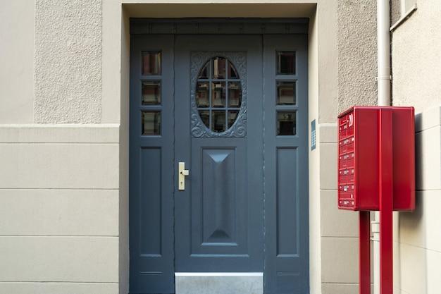 Uma vista de uma porta da frente azul e uma caixa de correio vermelha em um prédio de apartamentos.