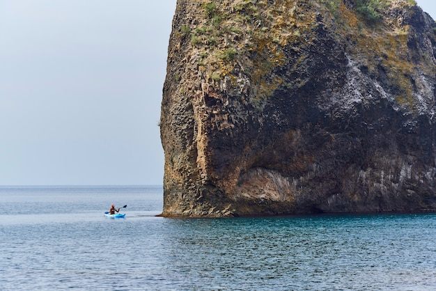 Uma vista do mar e um homem flutuante em um caiaque perto da rocha.
