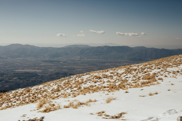 Uma vista do vale com a cidade vista do topo da montanha de neve.