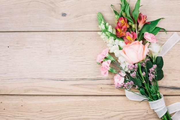 Uma vista elevada do buquê de flores coloridas amarrado com fita branca na mesa de madeira