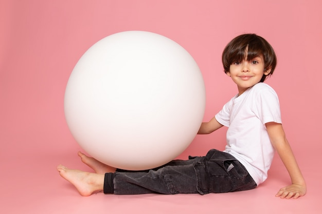 Uma vista frontal adorável menino bonitinho sorrindo em t-shirt branca jogando com bola branca na mesa-de-rosa