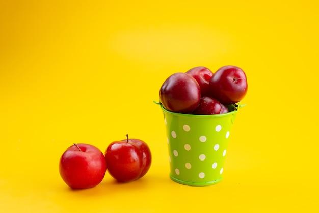 Uma vista frontal ameixas vermelhas frescas dentro de uma cesta verde em amarelo, cor de fruta azeda