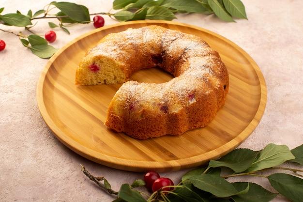 Uma vista frontal assada de bolo de frutas delicioso fatiado com cerejas vermelhas dentro e açúcar em pó em uma mesa redonda de madeira em rosa