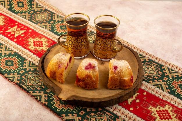 Uma vista frontal assada de bolo de frutas delicioso fatiado com cerejas vermelhas e açúcar em pó na mesa de madeira com chá rosa