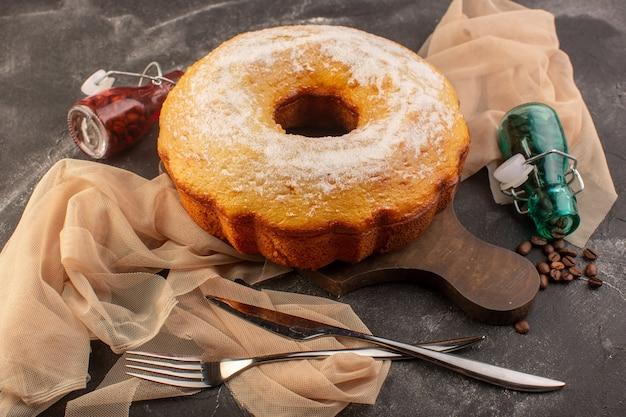 Uma vista frontal assada em um bolo redondo com açúcar em pó e sementes de café na mesa de madeira