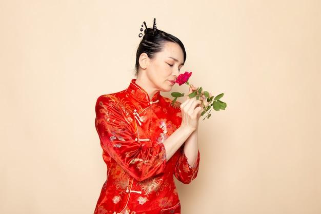 Uma vista frontal bela gueixa japonesa no tradicional vestido japonês vermelho com varas de cabelo cheirando a rosa vermelha elegante na cerimônia de creme de fundo divertido japão oriental