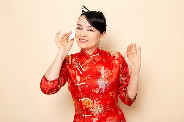 Uma vista frontal bela gueixa japonesa no tradicional vestido japonês vermelho com varas de cabelo posando segurando pouco algodão branco, limpando o rosto na cerimônia de creme de fundo japão