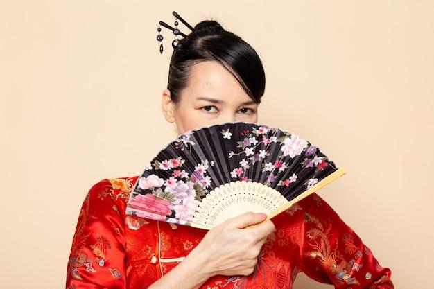 Uma vista frontal bela gueixa japonesa no tradicional vestido japonês vermelho com varas de cabelo posando segurando ventilador dobrável elegante sobre a cerimônia de creme de fundo japão