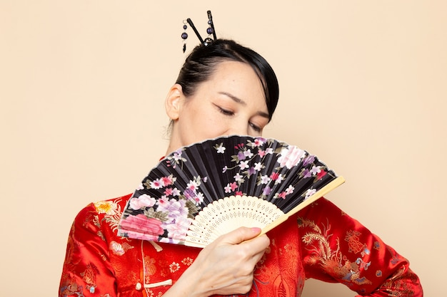 Uma vista frontal bela gueixa japonesa no tradicional vestido japonês vermelho com varas de cabelo posando segurando ventilador dobrável sorrindo sobre a cerimônia de creme de fundo japão