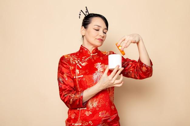 Uma vista frontal bela gueixa japonesa no vestido tradicional vermelho japonês com varas de cabelo posando creme de abertura pode sorrir sobre a cerimônia de creme de fundo japão