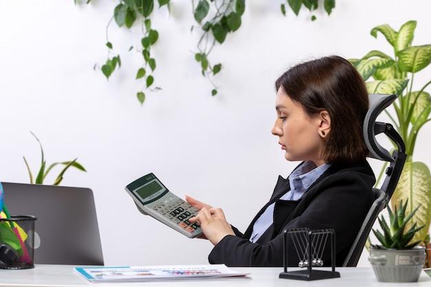 Uma vista frontal bela jovem empresária de casaco preto e camisa azul, trabalhando com a calculadora na frente do escritório de trabalho de negócios de mesa