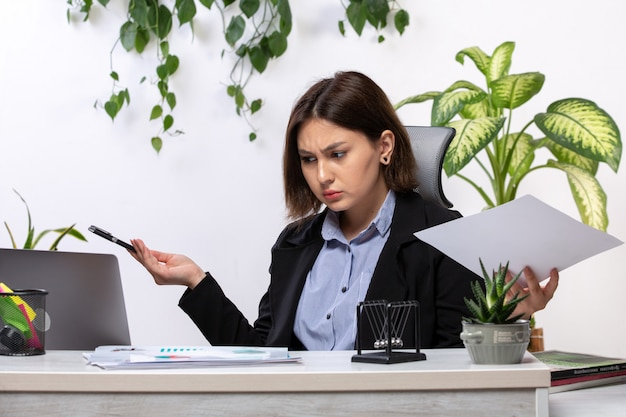 Uma vista frontal bela jovem empresária de casaco preto e camisa azul, trabalhando com o laptop na frente do escritório de trabalho de negócios de mesa