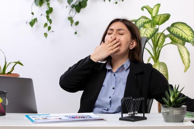 Uma vista frontal bela jovem empresária de jaqueta preta e camisa azul espirros na frente do escritório de trabalho de negócios de mesa