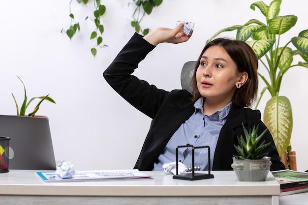 Uma vista frontal bela jovem empresária de jaqueta preta e camisa azul, jogando e jogando bolas de papel na frente do escritório de trabalho de negócios de mesa