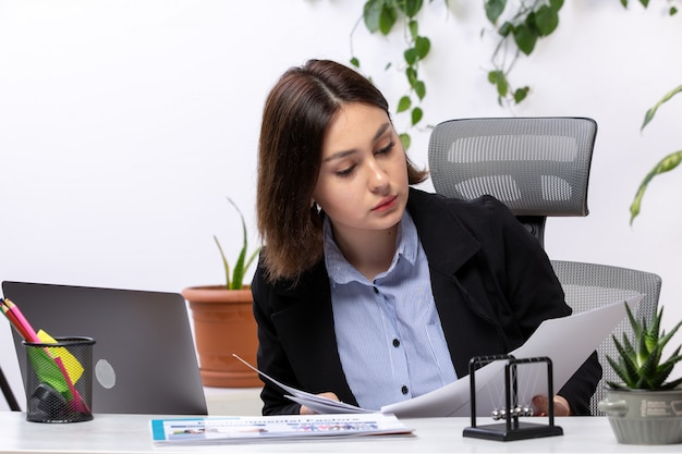Uma vista frontal bela jovem empresária de jaqueta preta e camisa azul, trabalhando com o laptop e documentos na frente do escritório de trabalho de negócios de mesa