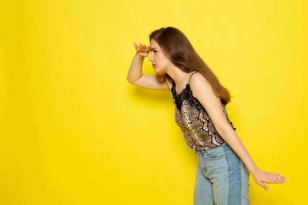 Uma vista frontal bela moça de blusa marrom e jeans azul, olhando para a distância