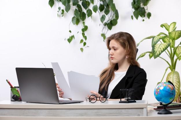 Uma vista frontal bela moça de camisa branca e jaqueta preta, trabalhando com documentos usando o laptop na frente da mesa com folhas penduradas