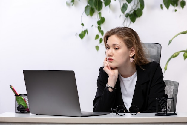 Uma vista frontal bela moça de camisa branca e jaqueta preta, usando seu laptop na frente da mesa com folhas penduradas