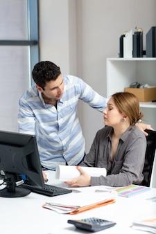 Uma vista frontal bela moça de camisa cinza, conversando e discutindo algo com o jovem dentro do escritório durante a atividade de trabalho diurno