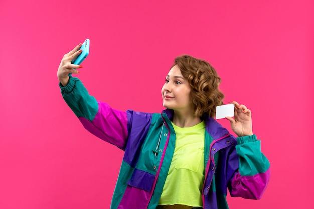 Uma vista frontal bela moça de camisa colorida de ácido calça preta jaqueta colorida tomando selfie sorrindo