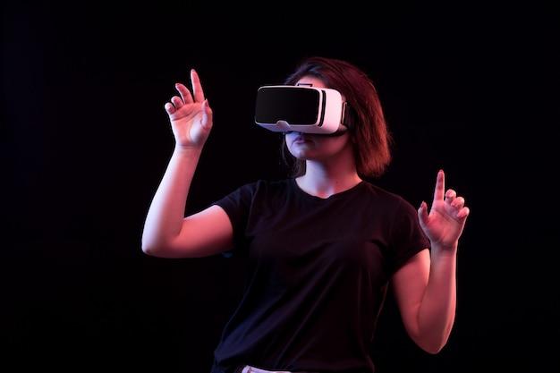 Uma vista frontal bela moça de camiseta preta, jogando jogando vr entretenimento jogos sobre o fundo preto
