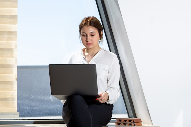 Uma vista frontal bela moça em calças de camisa branca, preto, sentado perto da janela, trabalhando no laptop durante o dia durante a atividade de trabalho de construção