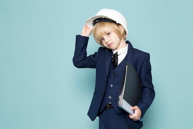 Uma vista frontal bonito rapaz de negócios em terno azul clássico posando segurando pasta preta negócios trabalho moda