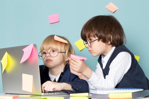 Uma vista frontal bonito rapaz de negócios em terno clássico azul posando na frente do laptop prata junto com outro garoto discutindo notas de colagem trabalhando negócios trabalho moda