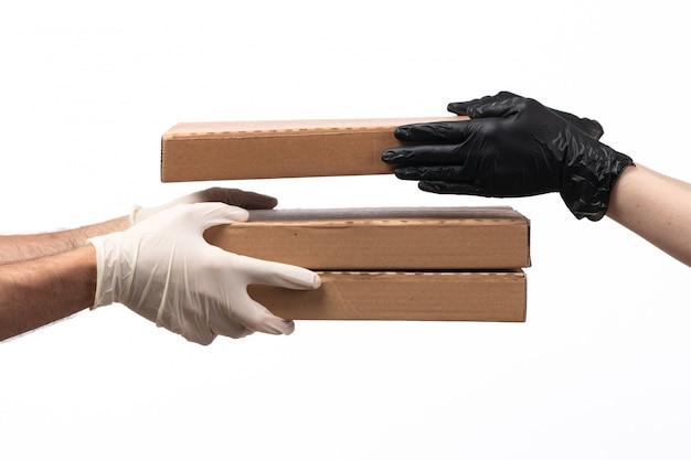 Uma vista frontal caixas de pizza marrom sendo entregues de mulher para homem