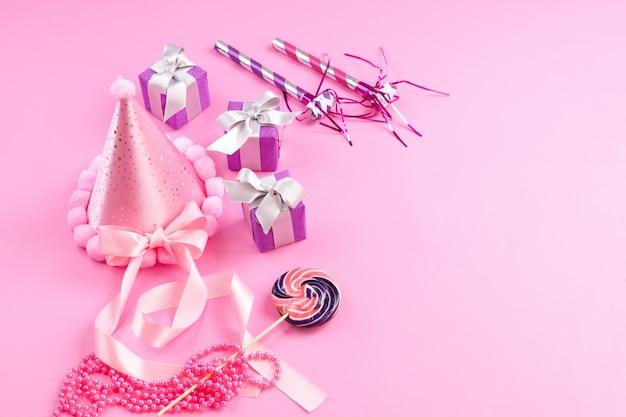 Uma vista frontal caixas de presente roxas, juntamente com o aniversário assobia pirulito boné rosa no rosa