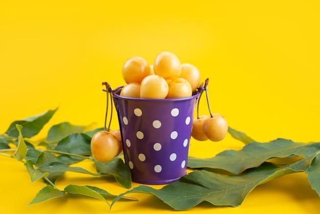 Uma vista frontal cerejas amarelas dentro de uma cesta roxa junto com folhas verdes na mesa amarela, cor de frutas verão