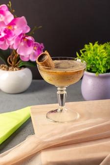 Uma vista frontal choco sobremesa marrom com sorvete dentro de vidro transparente, juntamente com flores no cinza