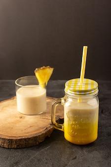 Uma vista frontal cocktail fresco gostoso bebida refrescante dentro pode com palha perto da mesa de madeira sobre o fundo escuro beber suco de verão