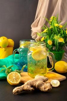 Uma vista frontal cocktail fresco limão bebida fresca dentro de copos de vidro fatias e limões inteiros, juntamente com flores sobre o fundo escuro