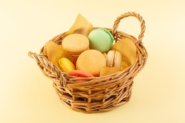 Uma vista frontal colorida de macarons franceses dentro de uma cesta na mesa amarela.