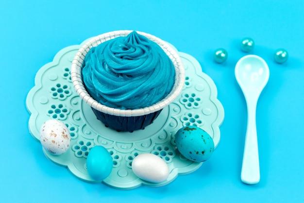 Uma vista frontal colorida de ovos junto com branco, colher isolada em azul, cor de desenho