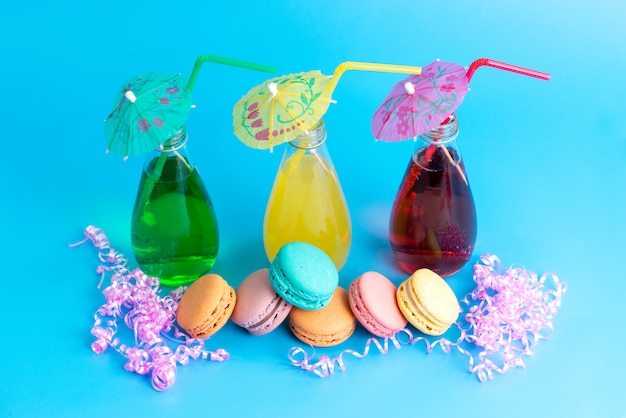 Uma vista frontal colorido cocktails com canudos, juntamente com macarons franceses em azul