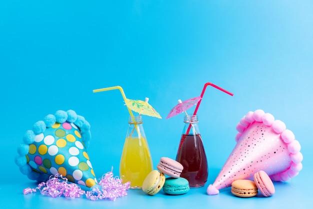 Uma vista frontal colorido cocktails de refrigeração com macarons franceses e bonés engraçados em azul