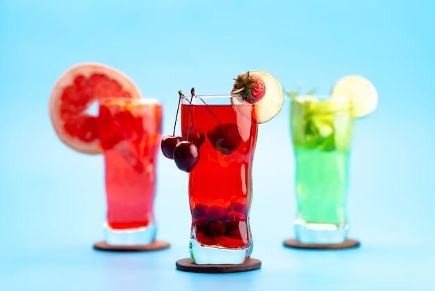 Uma vista frontal coquetéis de frutas frescas com fatias de frutas frescas resfriando no azul, beber suco de coquetel de cor de frutas