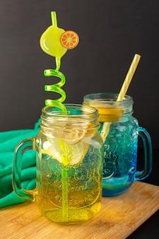 Uma vista frontal coquetel de limão bebida fresca e fresca dentro de copos de vidro fatiados e limões inteiros palhas no fundo escuro bebida de coquetel de frutas