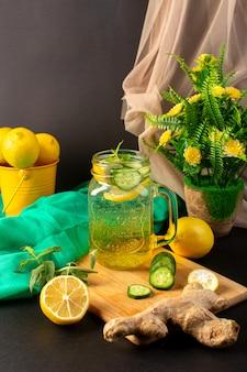Uma vista frontal coquetel de limão bebida fresca fresca dentro de copo de vidro em fatias e limões inteiros, juntamente com flores sobre o fundo escuro coquetel de frutas