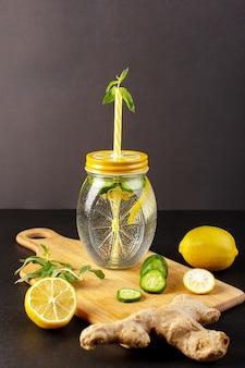 Uma vista frontal coquetel de limão bebida fresca fresca dentro de copo de vidro fatiado e limões inteiros pepinos junto com palha de flores sobre o fundo escuro coquetel bebida frutas